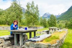 旅客妇女吃在自然的午餐在挪威山 库存图片