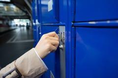 旅客妇女在蓝色大locke保留她的袋子和手提箱 免版税库存照片