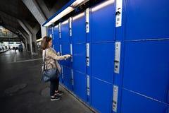 旅客妇女在蓝色大locke保留她的袋子和手提箱 库存照片