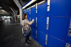 旅客妇女在蓝色大locke保留她的袋子和手提箱 免版税库存图片