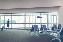 旅客妇女计划和背包看见飞机 库存照片