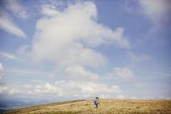 旅客帽子的行家女孩有背包的探索有薄雾晴朗的 免版税库存图片