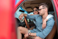 旅客年轻夫妇坐在汽车的太阳镜的 图库摄影