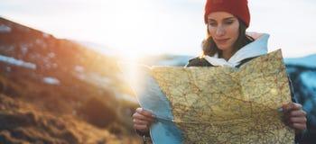 旅客手地图的女孩举行和神色太阳火光,人计划的旅行,背景自然的行家游人,享用旅途土地 免版税库存图片