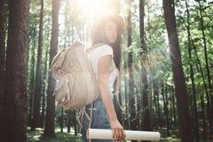 旅客有背包的行家妇女和帽子在手定位图和搜寻举行定向在树中在森林里 免版税库存照片