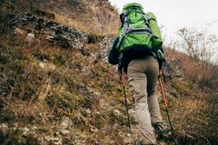 旅客有胡子的人迁徙和登山的图象在他的旅途期间的 背面图年轻男性远足在山 免版税库存图片