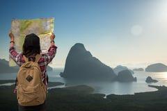 旅客游人有地图旅行的亚洲妇女看在日出的山景 免版税库存图片