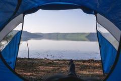 旅客的腿户外帐篷的 在我帐篷,湖和野营里面,夏日 免版税库存图片