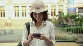 旅客背包徒步旅行者亚洲妇女旅行在曼谷,泰国 使用智能手机的愉快的年轻女性为谈话,读书和发短信 股票录像