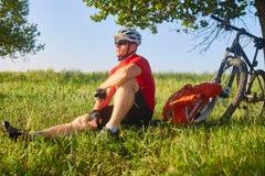 旅客骑自行车者有休息在与他的自行车的橡树下在他后在夏天下午 免版税库存照片