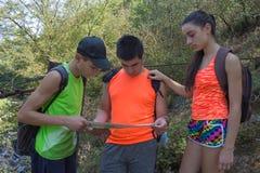 旅客,在度假读地图的远足者 有背包旅行的两个年轻游人 有背包旅行的三个年轻游人 库存图片