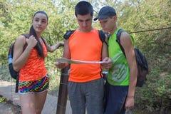 旅客,在度假读地图的远足者 有背包旅行的两个年轻游人 有背包旅行的三个年轻游人 免版税库存照片