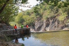 旅客,在水库附近的远足者 旅行冒险和远足暑假和我们的活动,活跃和健康生活方式 免版税库存照片