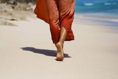 旅客` s脚在海滩走在海附近 免版税库存图片