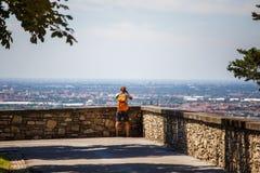 旅游人站立与他的在观察平台的后面在贝加莫在意大利并且拍在照相机佩带的短裤的一张照片, s 库存照片