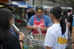 旅游吃popcicle在Chatuchak市场上在曼谷 免版税库存照片