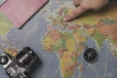 旅游在世界地图帮助下的计划假期与其他旅行辅助部件 指向北部欧洲的年轻女人  库存图片