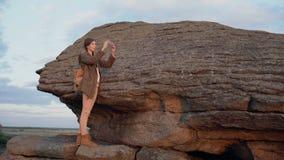 年轻旅游在她的智能手机照相机的妇女背包徒步旅行者拍摄的风景在远足在日落的岩石以后 股票视频