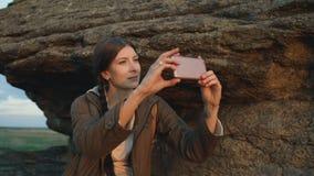 年轻旅游在她的智能手机照相机的妇女背包徒步旅行者拍摄的风景在远足在日落的岩石以后 股票录像