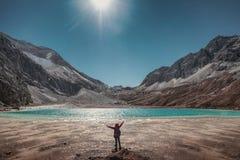 旅游培养手与绿松石湖和山脉在峰顶 库存图片