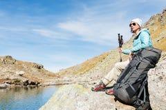 旅游女孩佩带的太阳镜下来夹克和帽子用一种背包和山设备有把柄的跟踪的 免版税库存照片