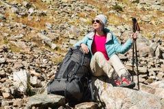 旅游女孩佩带的太阳镜下来夹克和帽子用一种背包和山设备有把柄的跟踪的 图库摄影
