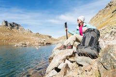 旅游女孩佩带的太阳镜下来夹克和帽子用一种背包和山设备有把柄的跟踪的 免版税库存图片