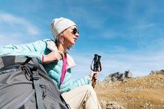 旅游女孩佩带的太阳镜下来夹克和帽子用一种背包和山设备有把柄的跟踪的 库存照片