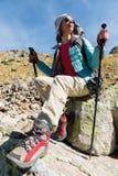 旅游女孩佩带的太阳镜下来夹克和帽子用一种背包和山设备有把柄的跟踪的 免版税图库摄影