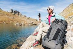 旅游女孩佩带的太阳镜下来夹克和帽子用一种背包和山设备有把柄的跟踪的 库存图片