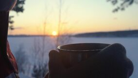 旅游女孩喝从热水瓶的茶在多雪的冬天森林里在日落 影视素材