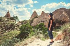 旅游女孩在卡帕多细亚的多小山区域显示方式在土耳其 远足,旅行,步行,休息 免版税图库摄影