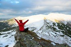 旅游女孩坐一块大灰色石头并且看山w 免版税图库摄影