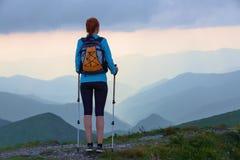 旅游女孩用后面大袋和跟踪棍子在草坪停留 美丽的天空 太阳光芒在山倒下 免版税库存图片