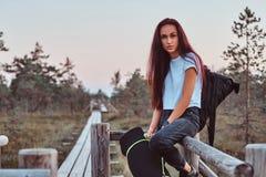 旅游女孩的画象倾斜在木篱芭的一件白色衬衣和牛仔裤的在美丽的秋天草甸在日落 免版税库存照片