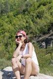 旅游妇女坐在山和放松的一块大石头 库存图片