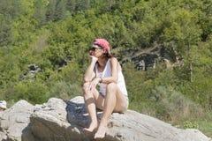 旅游妇女坐在山的一块大石头 库存照片