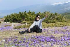 旅游妇女坐有紫色开花的番红花的一个草甸 免版税库存图片