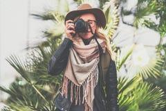 旅游妇女摄影师帽子的和有背包的站立室外在绿色植物背景并且拍照片 免版税库存图片