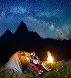 旅游家庭-看对的男人和妇女在晚上发光满天星斗的天空和银河在野营靠近营火 库存图片