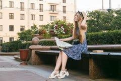 旅游少妇坐看地图的长凳 免版税库存图片