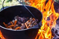 旅游常礼帽用在篝火的食物,烹调在远足,室外活动 肉饭的准备 免版税库存图片