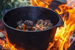 旅游常礼帽用在篝火的食物,烹调在远足,室外活动 肉饭的准备 图库摄影