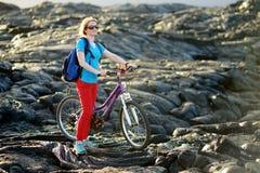 年轻旅游循环在夏威夷的熔岩荒野 朝向对熔岩观看的区域的女性远足者在她的自行车的Kalapana镇 库存图片