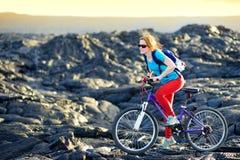 年轻旅游循环在夏威夷的熔岩荒野 朝向对熔岩观看的区域的女性远足者在她的自行车的Kalapana镇 免版税库存照片