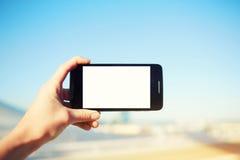 旅游手固定的单元电话,当拍摄风景的照片在夏天旅行时的 免版税库存图片