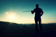旅游指南展示与杆的正确的方式在手中 有运动的背包立场的远足者在有薄雾的谷上的岩石观点 晴朗 免版税库存照片