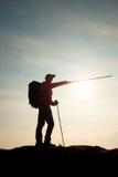 旅游指南展示与杆的正确的方式在手中 有运动的背包立场的远足者在有薄雾的谷上的岩石观点 免版税图库摄影