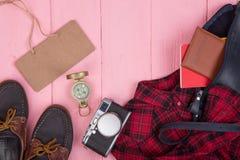 旅游材料-袋子、护照、照相机、指南针、鞋子、衬衣、笔记本和空白的黑板在木背景 库存图片
