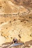 旅游看照相机的人上升的沙漠峡谷梯子 免版税库存图片